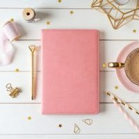 pink planner with coffee cup on table